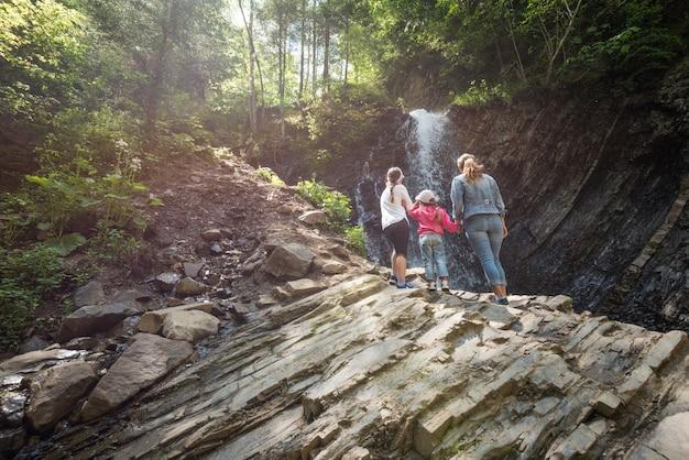 후면보기 어머니와 두 어린 딸이 산에 서서 화창한 여름 날에 산을 트레킹하는 동안 폭포의 요염한 경치를 즐기고 있습니다.