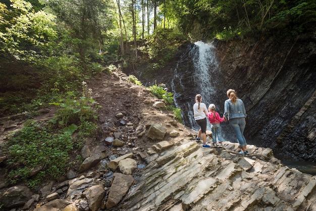뒷모습 어머니와 두 어린 딸이 산에 서서 산을 트레킹하면서 폭포의 매혹적인 경치를 즐기고 있습니다.