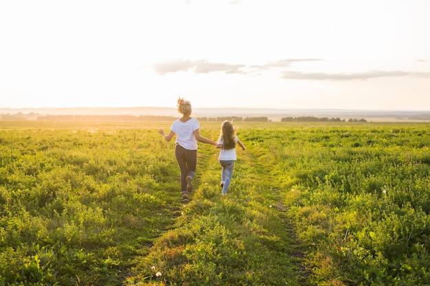 Rear view of mother and daughter running in green field with sunset