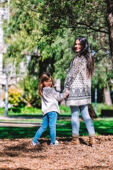 Rear view of mother and little daughter walking and holding hands in the park