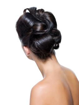 スタイリッシュな巻き毛の髪型を持つ大人の女の子の背面図