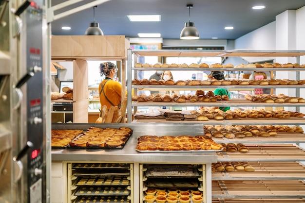오븐에서 갓 구운 빵과 케이크로 고객에게 빵을 판매하는 판매원과 카트를 판매하는 빵집의 후면보기