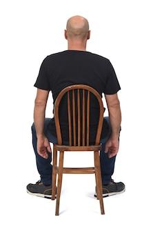 Вид сзади лысого человека, сидящего на белом пространстве,
