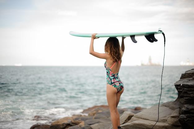 대서양 위의 머리에 서핑 보드와 함께 서있는 멀티 컬러 수영복에서 아름다운 소녀의 후면보기