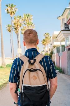 Вид сзади блондинки с рюкзаком, идущей по набережной лос-анджелеса с пальмами