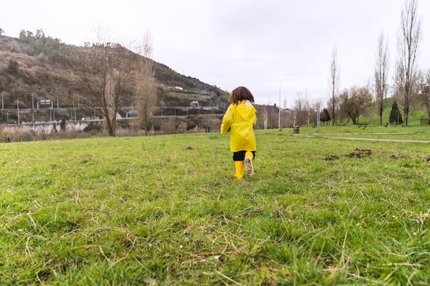 공원 잔디밭을 가로 질러 달리는 비옷과 노란 장화에 소년의 후면보기