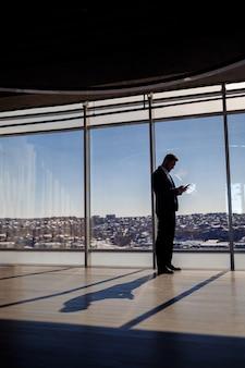 Вид сзади бизнесмена, глядя из большого окна с видом на город. у него в руках телефон. горизонтальный вид. выборочный фокус