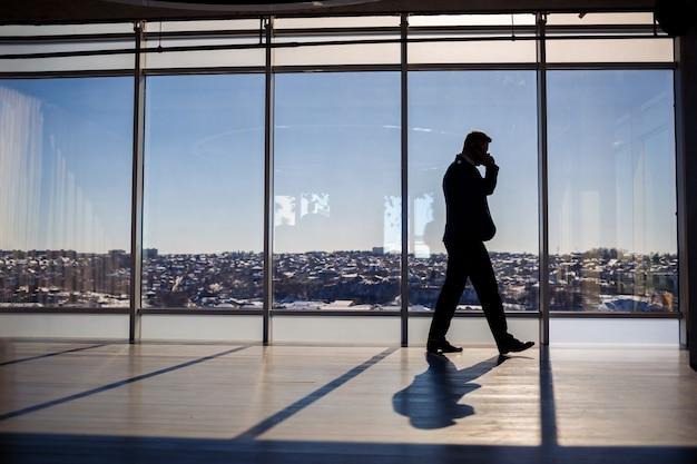 Вид сзади бизнесмена, глядя из большого окна с видом на город. у него в руках телефон. горизонтальный вид.