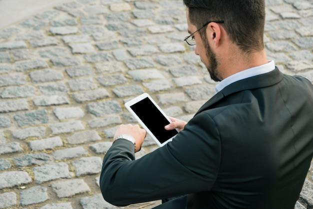 Вид сзади бизнесмена, стоя на асфальте, держа в руке мобильный телефон, проверка времени