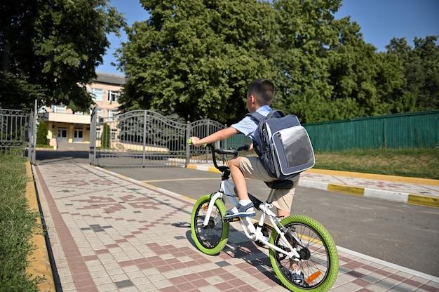早朝に自転車に乗っている子供の背面図。街で自転車に乗っている少年