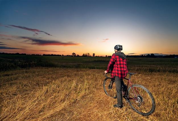 日没時のフィールドで砂利自転車に乗ってサイクリストの背面図