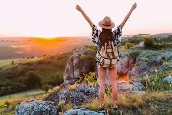 腕を上げた女性の登山者の後ろ姿