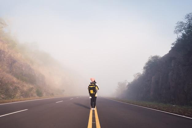 Вид сзади женщины-путешественницы, идущей посреди мощеной дороги.