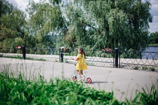 Вид сзади девушки в полный рост, едущей на скутере по дорожке вдоль пруда с деревьями, цветами и цветком ...