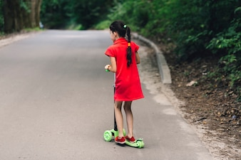 Rear view of a girl riding scooter on road