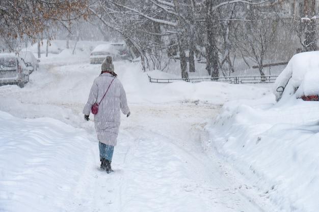 Вид сзади девушки, идущей по заснеженной улице москвы зимой