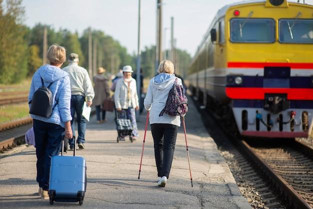 電車の旅を待っている高齢者のグループの背面図