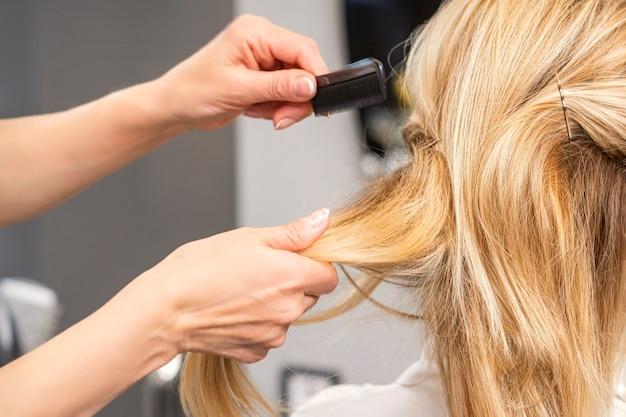 美容院で若い女性のブロンドの髪をとかす美容師の背面図