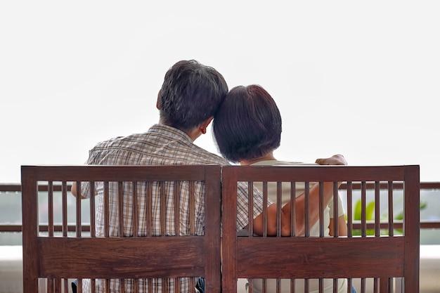Вид сзади счастливой азиатской пары средних лет на скамейке