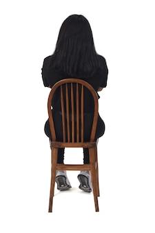 白い背景に腕を組んで椅子に座っているラテン女性の背面図、
