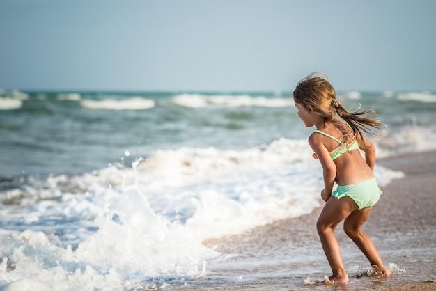 열대 국가에서 여름 방학 동안 따뜻한 여름날 바다에서 수영하는 어린 4 살짜리 소녀의 후면보기