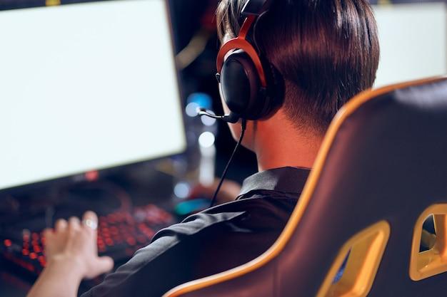 헤드폰을 끼고 앉아 온라인 비디오 게임을 하는 남성 사이버스포츠 게이머의 뒷모습