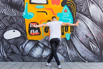Rear view of a man dancing on creative wall backdrop