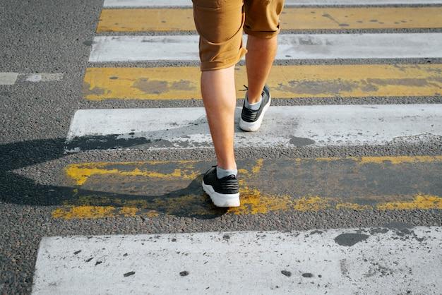 Вид сзади человека в шортах и кроссовках, переходящих дорогу по пешеходному переходу, крупный план мужских ног. выборочный фокус