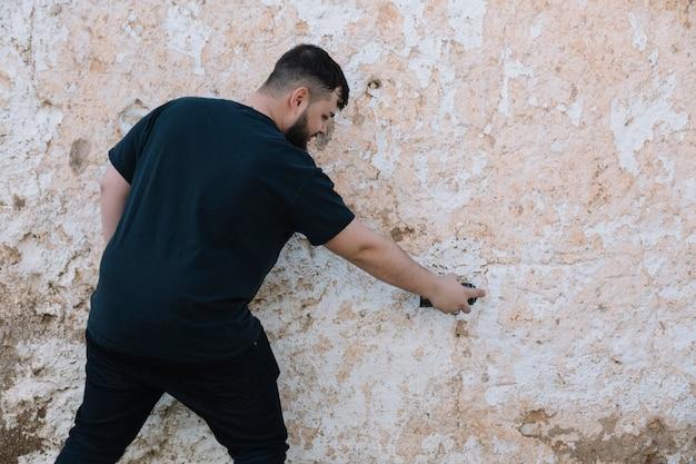 Вид сзади человека, рисующего граффити на поврежденной стене