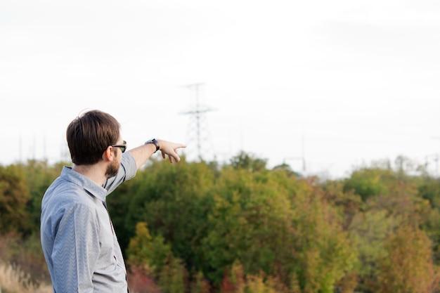 開いた田園地帯を指している男の背面図
