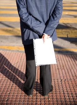 Вид сзади человека, стоящего на тротуаре, держа в руке белую папку