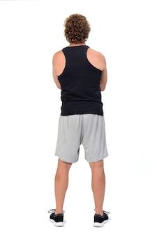 白いスペースにスポーツウェアのタンクトップとショートパンツを着ている男性の背面図、腕を組んで
