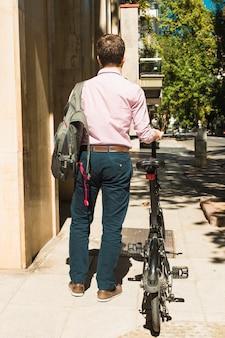 자전거와 함께 걷는 그의 배낭을 가진 남자의 뒷 모습