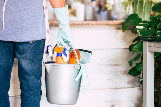 家事をしている保護手袋をした男の背面図。クリーニング製品が入ったバスケット
