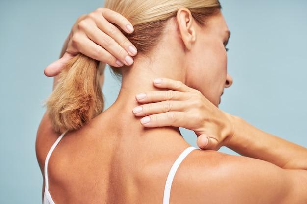 파란색 배경에 서 있는 동안 부드럽고 깨끗한 피부로 목을 만지는 성숙한 여성의 뒷모습