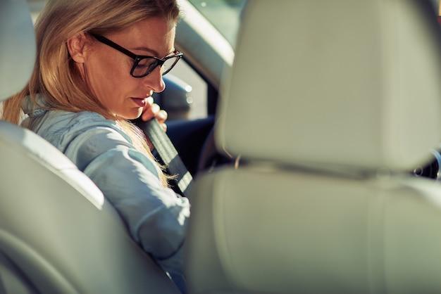 그녀의 차 운전대 뒤에 앉아 중년 백인 여성 비즈니스 여성의 후면보기