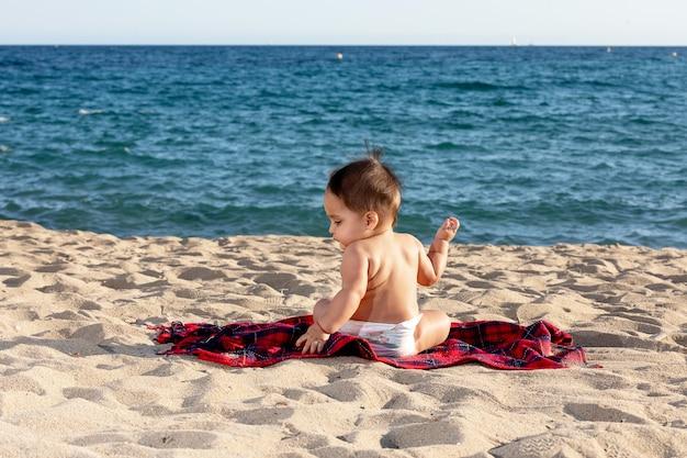 晴れた日にビーチでタオルの上に座っている新生児の背面図