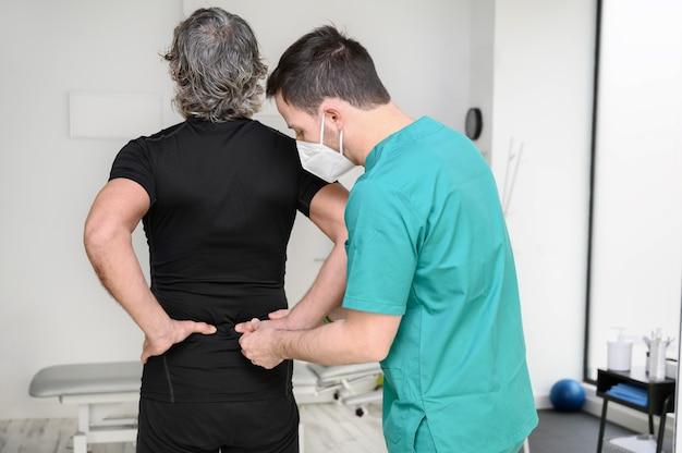 다시 남자를 검사하는 물리 치료사의 후면보기.