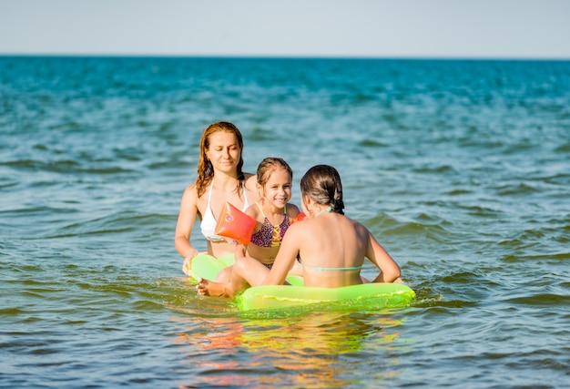 긍정적 인 젊은 가족 엄마와 두 어린 딸의 후면보기는 휴가 기간 동안 화창한 여름날 바다의 노란색 에어 매트리스에서 수영