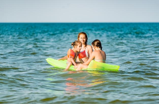 Вид сзади позитивной молодой семьи: мама и две маленькие дочери плавают