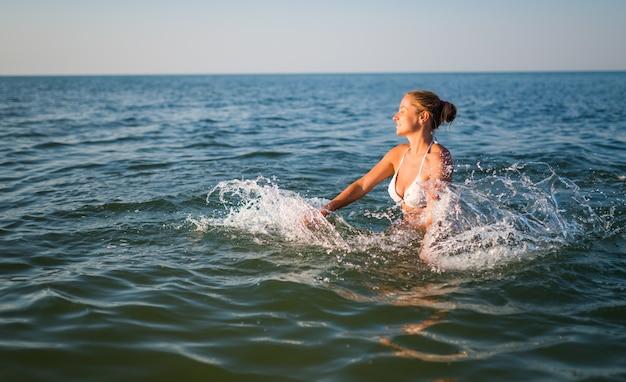 햇살 따뜻한 여름날에 바다에서 수영하는 예쁜 젊은 여자의 후면 볼 수 있습니다. 휴식의 개념과 관광 여행의 즐거움. copyspace