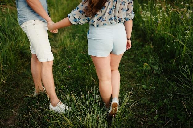 ロマンチックな男性と女性の背面図は、野原の芝生の上を散歩に立っています。手をつないで素敵な家族の概念。ランニングバックと目をそらしている若いカップル。