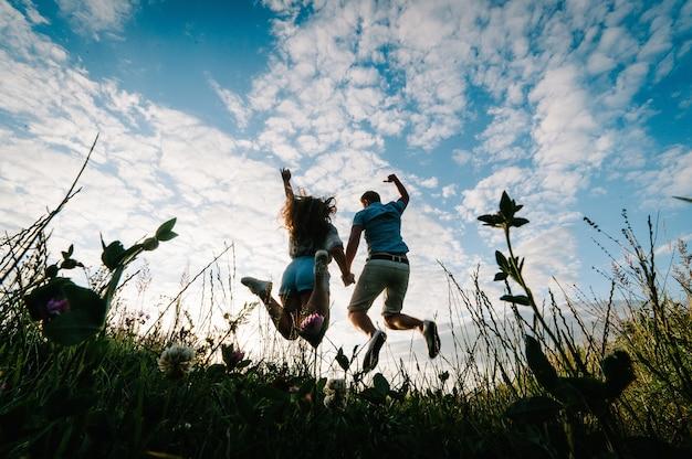 野原の芝生の上を歩いているロマンチックな男性と女性の背面図、素晴らしい夕日を楽しむ自然。手をつないで素敵な家族の概念。立ってジャンプする若いカップル。