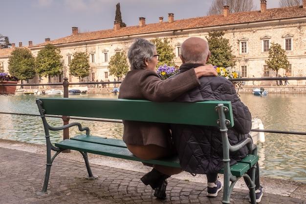 Вид сзади пожилой женщины, обнимающей своего мужа и смотрящей на пейзаж вместе с ним