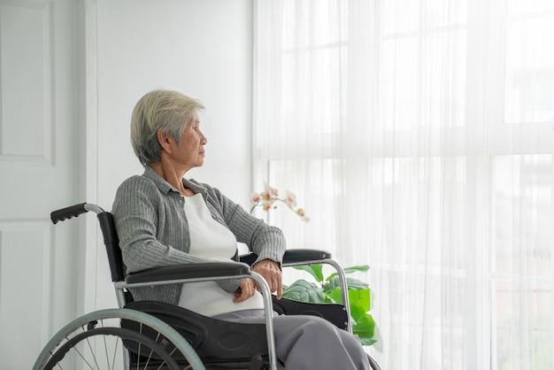 Вид сзади старшей женщины сидя на кресло-коляске смотря вне окна.