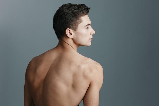 벌거 벗은 뒤를 가진 섹시한 남자의 뒷모습은 회색 배경에 옆으로 보입니다. 고품질 사진