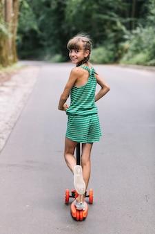 도로에 푸시 스쿠터를 타는 동안 다시 찾고 웃는 소녀의 후면보기
