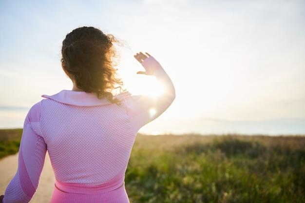 Вид сзади спортивной брюнетки, стоящей спиной к камере на фоне красивой природы с солнечным закатом, в прекрасный вечерний летний день