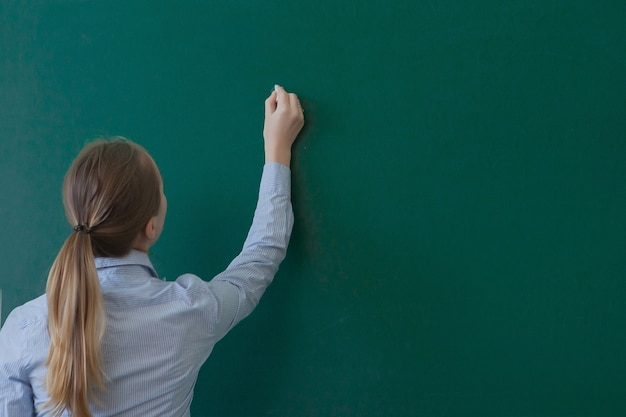 Вид сзади студент или преподаватель с длинными волосами брюнетка, писать на пустой зеленой доске или доске с copyspace