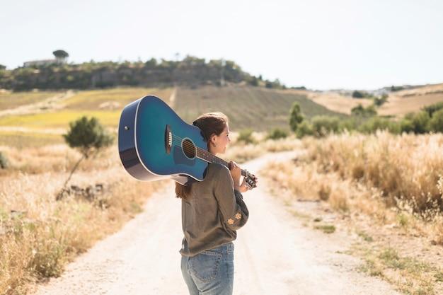 비포장 도로 들고 기타에 서있는 십 대 소녀의 후면보기